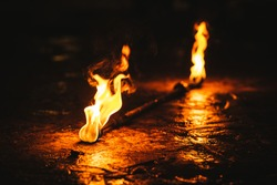 Fire poi performance. Burning poi / torch on the ground
