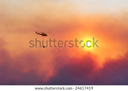 Fire rescue helicopter damping fire against sunset. Shot near Stellenbosch, Western Cape, South Africa.