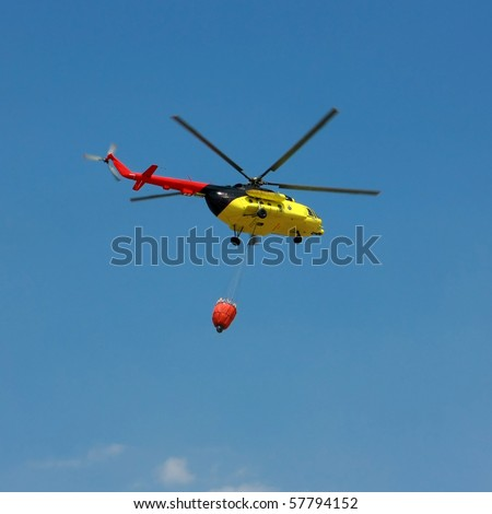 Fire rescue helicopter with water bucket - Square crop All copyrighted elements removed - stock photo