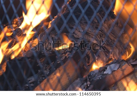 fire safely behind a mesh grill, burning wood and papers