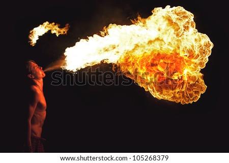 Fire show artist breathe fire in the dark - stock photo