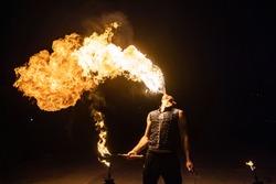 Fire show artist breathe fire in the dark jamp