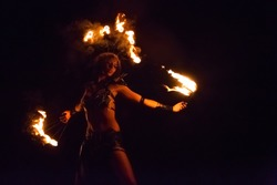Fire show artist on the beach fire in the dark
