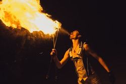 fire show, dancing with flame, male master fakir with fire works, performance outdoors, flame control man, a man in a suit LED dances with fire, draws a fiery figure in the dark