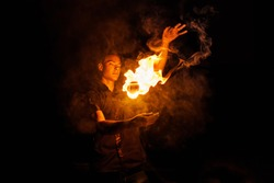 Fire show. Fakir juggles with fire Poi. Night performance. Illusion of a suspended object