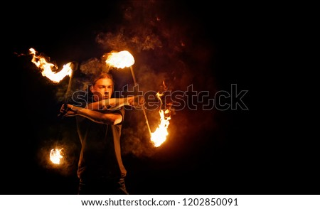 Fire show. Fire dancer dances with. Night performance. Dramatic portrait. Fire and smoke.