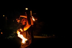 Fire show. The fakir juggles Poi. Night performance. Dramatic portrait. Heat and danger.