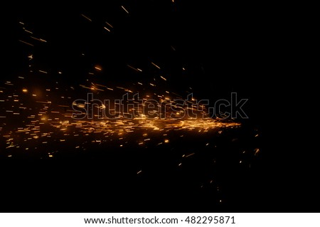Fire sparks on a black background during metal cutting, hot burning element in flame  #482295871