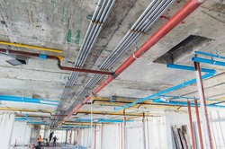 Fire sprinkler system with red pipes is placed to hanging from the ceiling inside of an unfinished new building.Installation of conduits in buildings.Conduit system in building under construction.