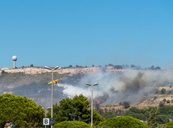 fire starts on the hills of Marseille, near Marignane airport. yellow fire-fighting plane is throwing water on it.