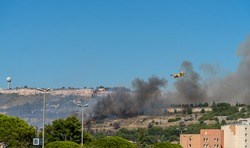 fire starts on the hills of Marseille, near Marignane airport. yellow fire-fighting plane is going to throwing water on it.
