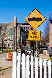 Fire station sign on city street with church building and construction in background - yellow sign with fire engine icon is crinkled and grungy with sticker of face where driver should be.