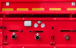 Fire truck. Rescue engine. Side view of red firetruck vehicle. Fire department truck. High pressure fire safety pump, gauge pressure, and valve lever on firetruck. Reflective tape for safety on truck.
