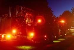 Fire truck with flashing red lights of a fire engine night time in dusk