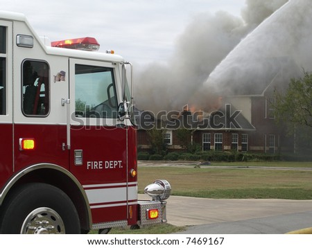 Fire truck with house on fire.