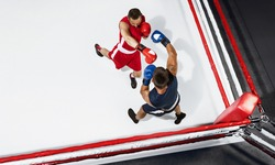 Fire. Two professional boxers boxing on white background on the ring, action, top view. Couple of fit muscular caucasian athletes fighting. Sport, competition, excitement and human emotions concept.