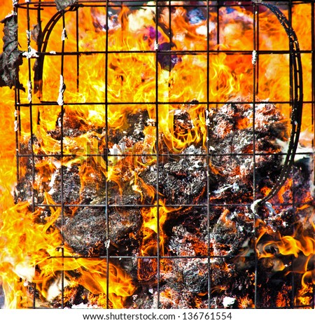Fire with flames and remains of a burning container - stock photo