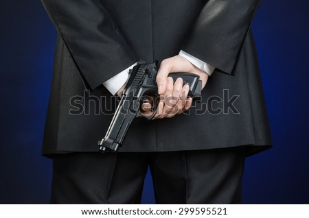 Firearms and security topic: a man in a black suit holding a gun on a dark blue background in studio isolated