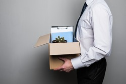 fired businessman packing office supplies in cardboard box at workplace