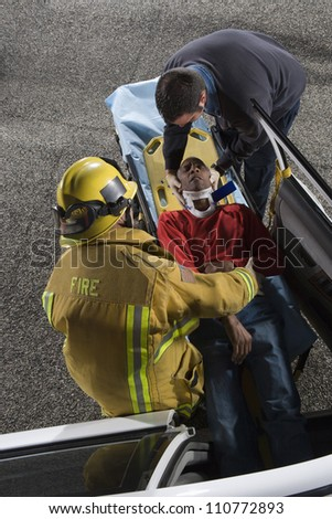 Firefighter and doctor taking out victim from car