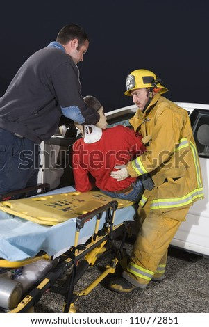 Firefighter and doctor taking out victim from damaged car