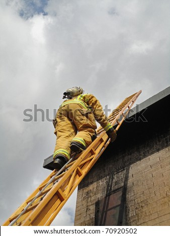 Firefighter ascends on a twenty-four wooden extension ladder.
