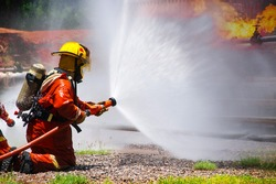 FIrefighter Fighting a Fire During a Firefighting Training Exercise for Safety Danger, Fire Insurance Concept