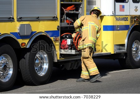 Firefighter getting equipment from his fire truck