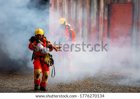 Firefighter hero carrying baby girl out from burning building area from fire incident. Rescue people from dangerous place ストックフォト ©