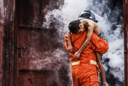 Firefighter holding  child boy to save him in fire and smoke,Firemen rescue the boys from fire. Fire prevention and extinguishing concept