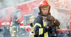 Firefighter in fire fighting operation. Portrait of heroic fireman in protective suit and red helmet holds saved cat in his arms, second fireman is out of focus near fire engine