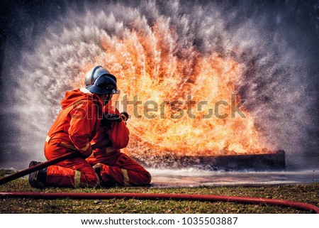 Firefighter in fire fighting suit spraying water, Firemen fighting  raging fire with huge flames of burning, Fire prevention and extinguishing concept