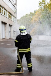Firefighter in uniform watering a fire hose during exercises