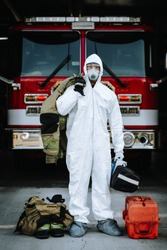 Firefighter in white protective, tyvek style suit, mask, and eye protection holding turnouts and medical gear during the Covid-19 pandemic.