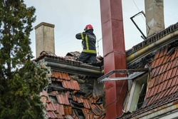 Firefighter inside a collapsed roof of a house is looking for survivors. House rooftop damage. Charred roof trusses and burnt furniture. A blazing fire burns roof rafters. Translation:''Firefighters''