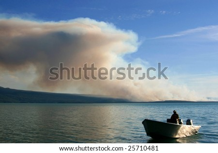 Firefighter On Boat Near Large Wildfire
