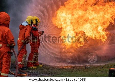 Firefighter Put on a  suit Orange Extinguish Car oil fire oil spillage hydrant From accident Car crash prevent practice Safety 3 people Control Blackout alarm blaze assistance heat