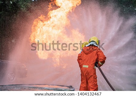 Firefighter Put on a suit Orange Extinguish Car oil fire oil spillage hydrant From accident Car crash prevent practice Safety 3 people Control Blackout alarm blaze assistance heat putting out Stockfoto ©
