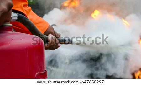 Firefighter putting out a fire with a powder type extinguisher.  Stockfoto ©