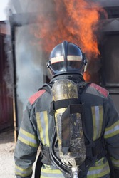 Firefighter putting out fire training station extinguisher backdraft emergency safety drill procedure.