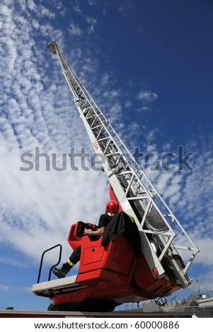 Firefighter serving with the fire truck ladder extended.