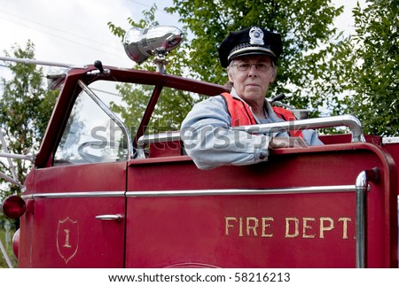 firefighter sitting in an old retro firetruck