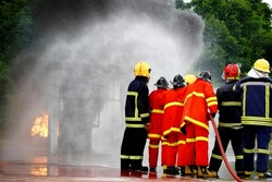 Firefighter spraying water to fire for heat protection, Team fireman training fighting fire.