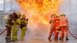 firefighter training., fireman using water and extinguisher to fighting with fire flame in an emergency situation., under danger situation all firemen wearing fire fighter suit for safety.