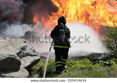 Firefighter trying to put water on a big fire