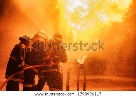 Firefighter using extinguisher or Twirl water fog type fire extinguisher to spray water from hose for fire fighting with fire flame on fuel and control fire for safety in plant of industrial area.