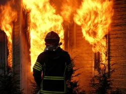 Firefighter watches old, abandoned house burning down.