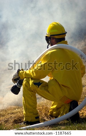 firefighter with hose on ready monitoring prescribed burn