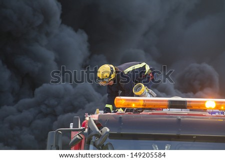 firefighter working over a truck during a fire