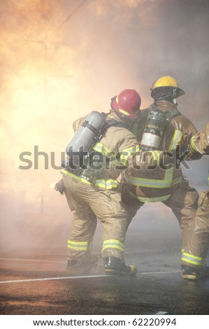 Firefighters attack a propane fire.